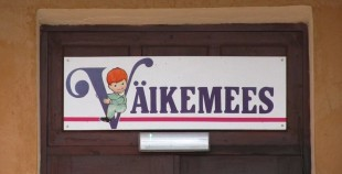 "Seen on a street in the north-eastern Estonian city of Kohtla-Järve. What could be behind a door with a sign above it reading Väikemees (Little Man)? The building is surrounded by an enclosed yard and has playground equipment in the back. My first thought: ""Could this be a private boys kindergarten?"" Photo: Riina Kindlam"