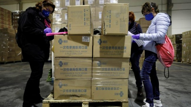 Workers sort out all the personal protective equipment (PPE) received from China at a warehouse in Valencia, Spain, on Mar. 25 2020. A total of 3,800,000 masks, 5,000 protective suits and 2,000,000 gloves arrived to Valencia region to equip hospitals and elderly homes. Photo: Juan Carlos Cardenas/EPA/CP