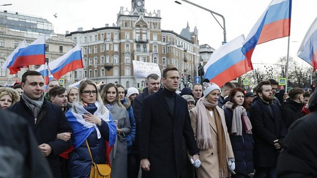 Russian opposition activist Alexei Navalny, centre, and his wife Yulia, right of him, take part in a march last year in memory of assassinated opposition leader Boris Nemtsov. Navalny, himself, has survived a poisoning and has been imprisoned. (Pavel Golovkin/AP)