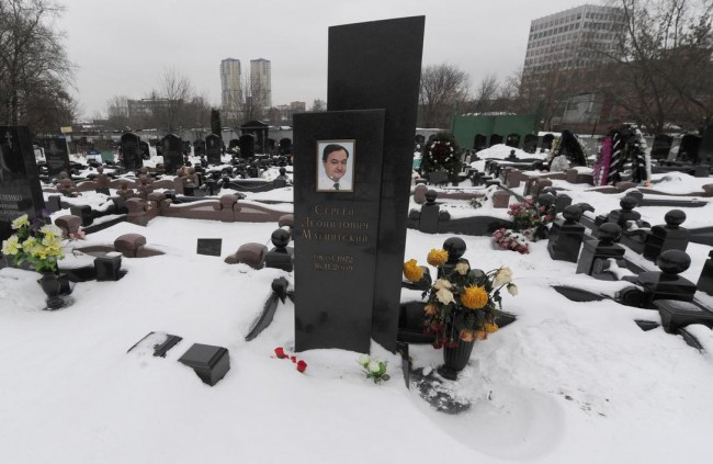 "A picture taken on Dec. 7, 2012, shows snow clad grave of Russian lawyer Sergei Magnitsky with his portrait on the tomb (C) at the Preobrazhenskoye cemetery in Moscow. Magnitsky legislation ""places responsibility for corruption and human rights abuse on individuals instead of punishing entire nations with broad sectoral sanctions,"" writes Marcus Kolga.  ANDREY SMIRNOV / AFP/GETTY IMAGES"