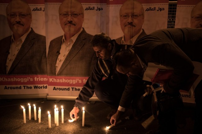 People light candles in front of posters of Jamal Khashoggi during a candle-light vigil to remember journalist Jamal Khashoggi outside the Saudi Arabia consulate on October 25, 2018 in Istanbul, Turkey. (Chris McGrath/Getty Images)