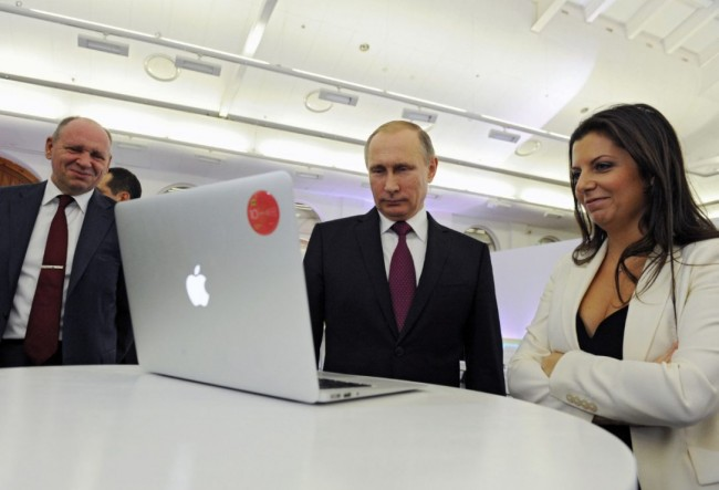 In this December, 2015 file photo, Margarita Simonyan, the editor-in-chief of state-funded RT television network, right, Russian President Vladimir Putin, centre, and Kremlin's first deputy chief of staff, Alexei Gromov, left, attend an exhibition marking RT's 10th anniversary in Moscow. The Kremlin voiced dismay Thursday Nov. 30, 2017 over the withdrawal of a Russian state-funded TV station's credentials in the U.S. and warned of a quick retaliation.  (MIKHAIL KLIMENTYEV / AP)