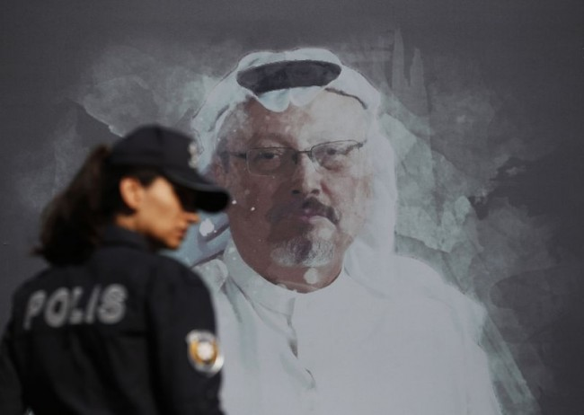 A Turkish police officer walks past a picture of slain Saudi journalist Jamal Khashoggi prior to a ceremony, near the Saudi Arabia consulate in Istanbul, marking the one-year anniversary of his death.  LEFTERIS PITARAKIS/THE ASSOCIATED PRESS via The Globe and Mail