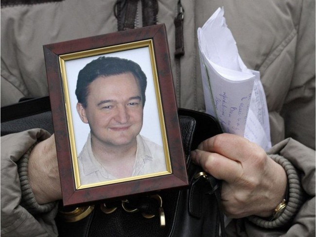 In this November 2009 file photo, a portrait of lawyer Sergei Magnitsky, who died in a Russian jail, is held by his mother Nataliya Magnitskaya, as she speaks during an interview with the AP in Moscow. ALEXANDER ZEMLIANICHENKO / AP / www.ottawacitizen.com