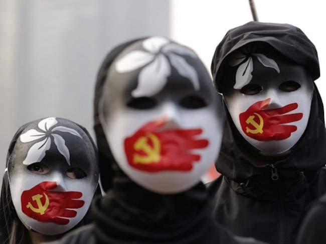 People wearing masks stand during a rally to show support for Uighurs and their fight for human rights in Hong Kong, Sunday, Dec. 22, 2019. LEE JIN-MAN / The Associated Press