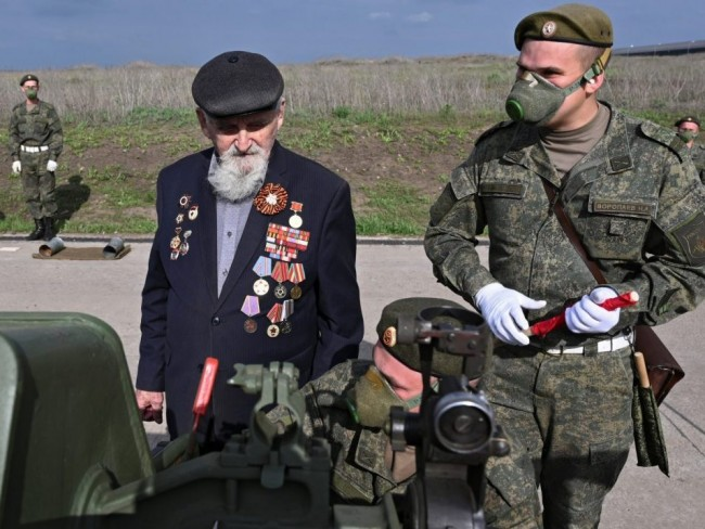 Second World War veteran Ivan Chubov, 94, examines an artillery piece as he attends exercises of artillery crews ahead of the Victory Day celebrations, amid the COVID-19 outbreak, at a range in Rostov Region, Russia, Thursday, May 7, 2020.Sergey Pivovarov / Reuters