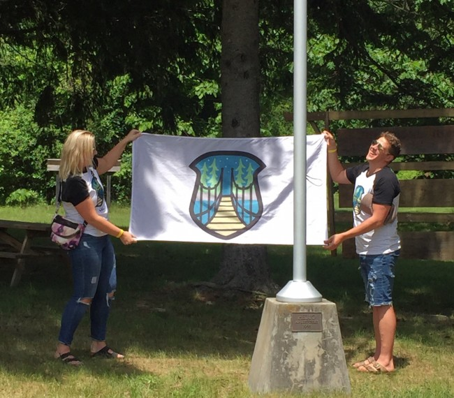 "Two of the inaugural ""JK Alumni Laager"" (JKAL) organizers, Anneliis Põldre and Paul Lillakas, show off the brand-new JKAL flag with its custom logo, designed by Ashley Lennox.  Photo credit:  Kristina Põldre (2018)"