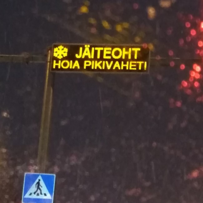 When the temperature is around null (zero, the freezing mark, 32°F), this sign above Sõle tänav in Põhja-Tallinn lights up. Photographed through an icy tuule/klaas (windshield) while waiting punase tule taga (at a red light), it was mounted this past fall above the valgus/foorid (traffic lights) and jala/käijate üle/käigu/rada (pedestrian crosswalk) where crowds of kids cross to and from Pelgu/linna Gümnaasium (High School). Foto: by Riina Kindlam (2019)