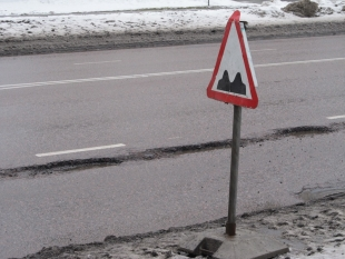 "What does the road sign mean? Ettevaatust, kaks muhku teel? – Attention, two bumps in the road ahead? Or brace yourself for a kraater? It actually means be ready for anything; rough roads, i.e surprises ahead. Surprises that were not there yesterday. In this case, a trio of potholes in the alfaldist tee/kate (asphalt pavement or road surface), which looks to be just the right size to swallow your tire perfectly and give you a terrific jolt, i.e. the term löök/auk – ""strike hole"". Photo: Riina Kindlam"