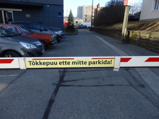 """Do not park in front of the <tõkke/puu>."" The bar (<puu>) is a barrier which stops you (<tõkestab sind>) from passing through. In this case, it controls entry into the <parkla> or <parkimis/plats> of the Vanemuise teater in Tartu."